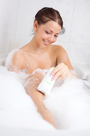 beautiful young brunette woman taking a relaxing bath and deleting hair with electric epilator photo
