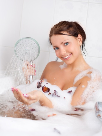 beautiful young brunette woman taking a relaxing bath with foam and rose petals photo