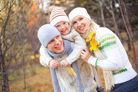 fall fun: happy young family spending time outdoor in the park (focus on the father) Stock Photo