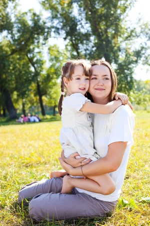 beautiful young mother and her daughter in the park on a sunny autumn day photo