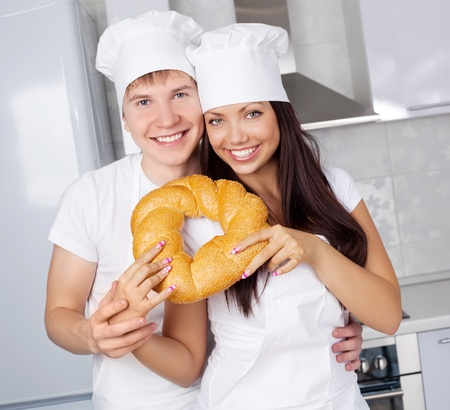 two happy young bakres with bread in the kitchen photo