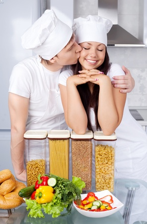 two happy young cooks in love in the kitchen photo