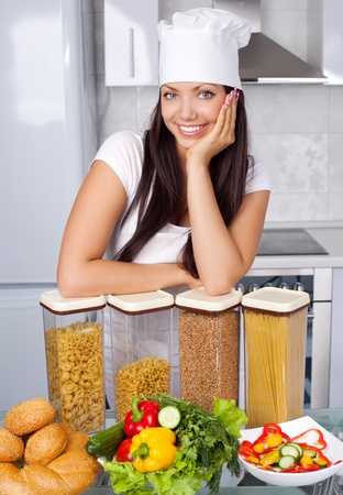 beautiful young cook with pasta and vegetables in the kitchen photo
