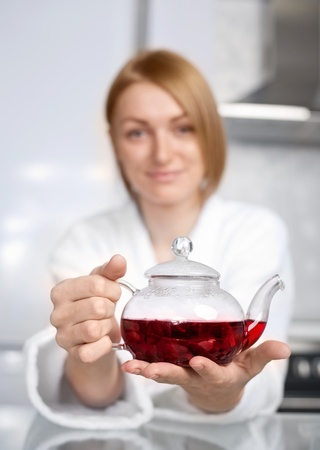 beautiful happy young woman drinking tea at home in the morning (focus of the teapot) photo