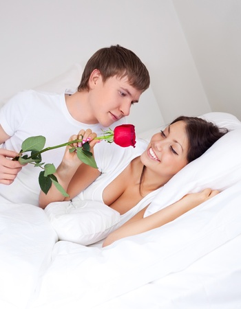 young man kissing his beautiful girlfriend and giving her a rose (focus on the woman) photo