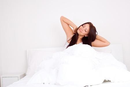 ragazza piuttosto felice svegliarsi al mattino e stretching Archivio Fotografico
