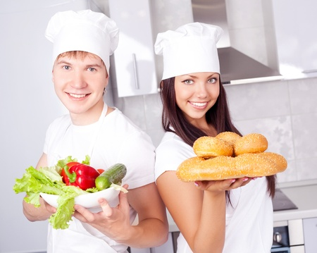 two happy young cooks with bread and vegetables in the kitchen photo