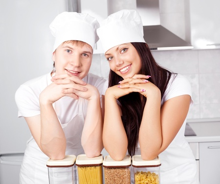 two happy young cooks in the kitchen photo