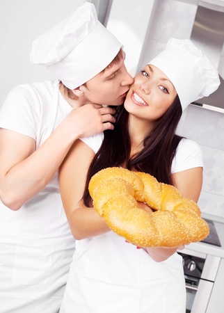 two happy young bakers with bread in the kitchen photo