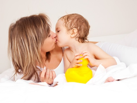 young beautiful mother and her baby on the bed at home after the shower Stock Photo - 8332084