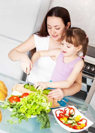 young mother and her five year old daughter cook together on the kitchen at home photo