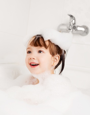 beautiful little girl taking a relaxing bath with foam   photo