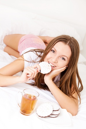 beautiful young woman eating breakfast in bed  photo