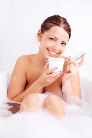 body scrub: beautiful young brunette woman taking a relaxing bath with foam and applying body scrub