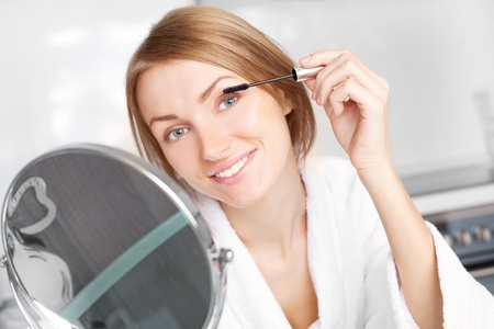beautiful young woman looking into the mirror and applying mascara Stock Photo - 8402456