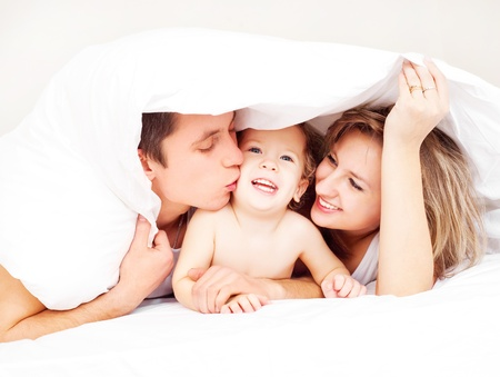 family baby: happy family, mother ,father and their baby under the blanket on the bed at home (focus on the man)