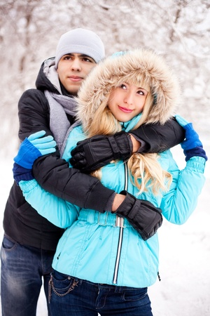happy young beautiful couple having a walk in winter park (focus on the girl) photo