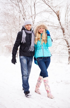 happy young beautiful couple having a walk in winter park (focus on the woman) Stock Photo - 8445262
