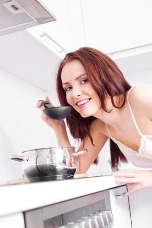 beautiful young woman cooking dinner in the kitchen photo