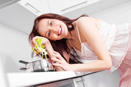 beautiful young woman cooking soup in the kitchen photo