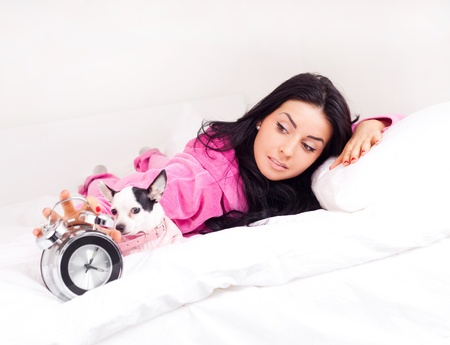 beautiful young brunette woman with her dog on the bed waking up in the morning photo
