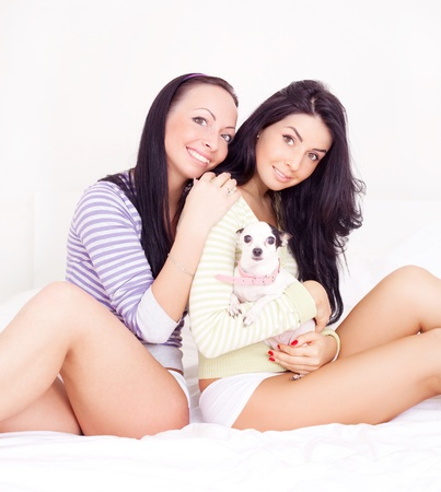 beautiful  brunette girls with their dog on the bed photo