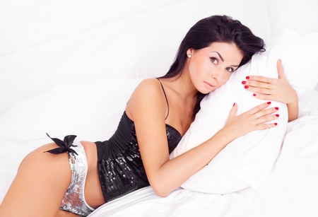 sexy young brunette woman wearing underwear on the bed at home photo