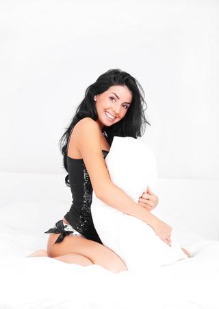 mujer en la cama: sexy Morena joven vistiendo ropa interior, abrazando una almohada sobre la cama en su casa
