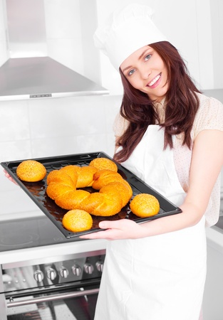 beautiful young woman baking bread  in the kitchen photo