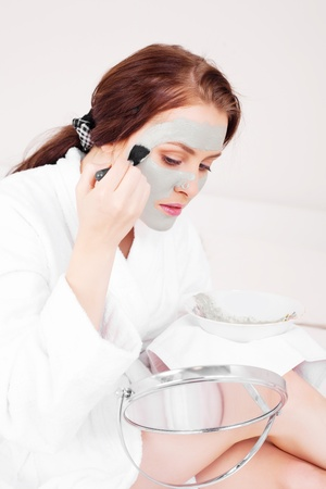 young woman applying a deep cleansing clay mask with a brush photo