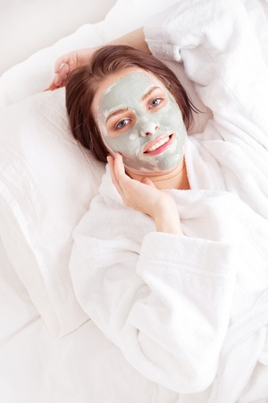 young woman wearing a deep cleansing green clay mask  photo