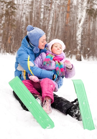 happy family; young mother and her daughter skiing and having fun in the winter park (focus on the child) photo