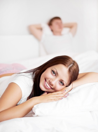 happy young woman and  sleeping man on the bed at home (focus on the woman) Stock Photo - 8563123