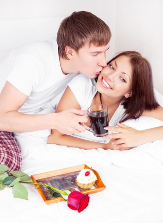 young man bringing his girlfriend a rose and coffee and waking her up photo