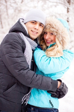 happy young beautiful couple having a walk in winter park (focus on the man) photo