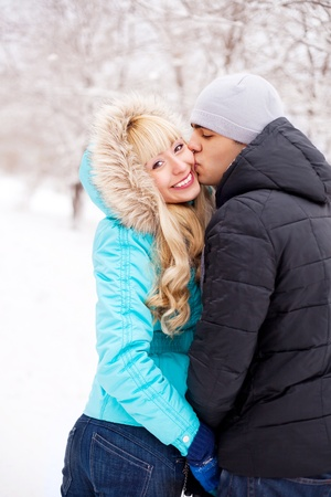 happy young beautiful couple having a walk in winter park (focus on the woman) photo