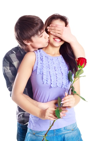 happy beautiful  teenage couple, a boy giving a rose to his girlfriend and kissing her   photo