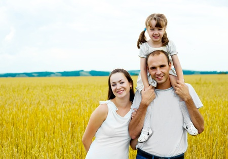 happy family; young mother, father and their daughter having fun at the wheat field (focus on the woman) Stock Photo - 8625075