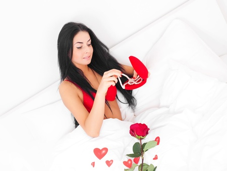 beautiful brunette woman waking up at home on a Valentines day with presents and a rose near her, prepared by her husband photo