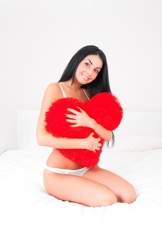 sexy young brunette woman with a heart shaped pillow on the bed at home photo