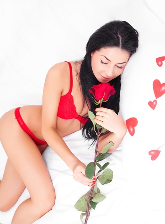 sexy young brunette woman with  hearts and a rose on the bed at home photo