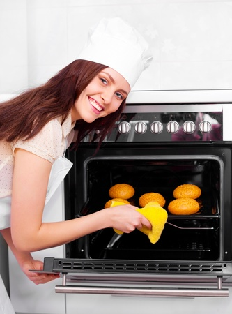 beautiful young woman baking bread in the kitchen at home photo