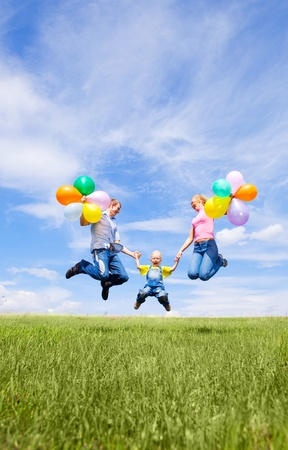 happy jumping family with balloons outdoor on a summer day Stock Photo - 8732636