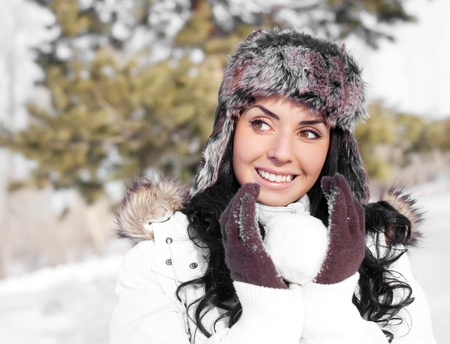 pretty young brunette woman playing snowballs in winter outdoor photo