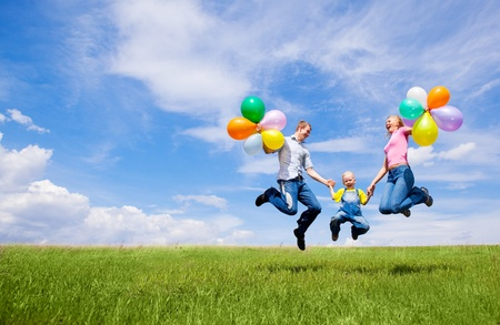 fun colors: happy jumping family with balloons outdoor on a summer day