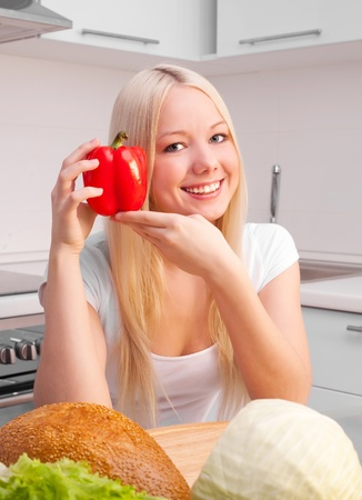 beautiful young blond woman with a pepper and bread in the kitchen at home Stock Photo - 8860546