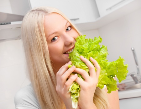 beautiful young blond woman eating salad in the kitchen at home Stock Photo - 8860549