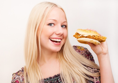 happy young woman eating a hamburger with chicken,  isolated against white background photo