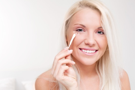 beautiful young blond woman applying cream on her face at home Stock Photo - 8860577