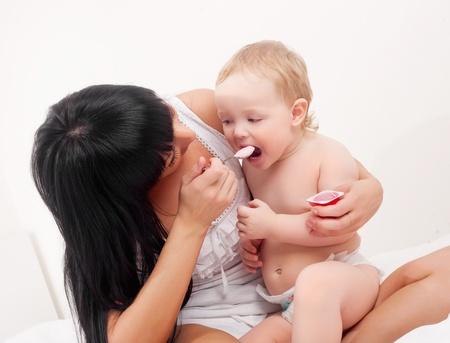 happy young mother feeding her baby with yogurt Stock Photo - 8860604